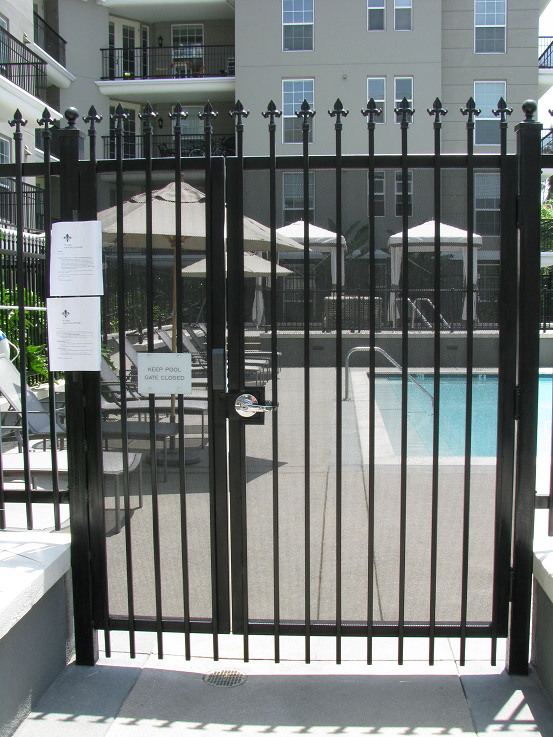 Wrought iron pool gates with lock assemblies and self closing hinges. Screen covers the gate and side panel to prevent reach through to the lock.